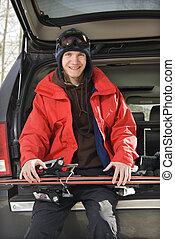 Teenager holding skis. - Caucasian male teenager sitting on...