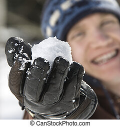 Teenager holding a snowball - Caucasian male teenager...
