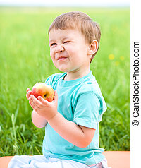 Portrait of a happy little boy with apple