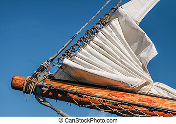 Bowsprit and gathered sail of a large sailing ship in...