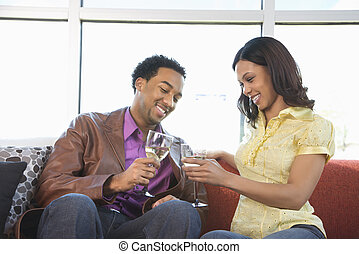 Couple toasting glasses. - African American couple toasting...