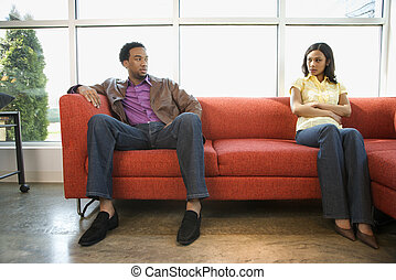 Disputing couple - African American couple sitting on couch...