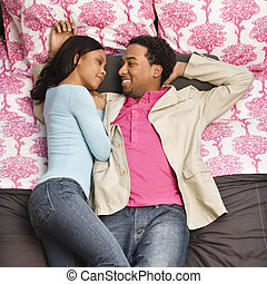 Couple laying on bed. - African American couple laying on...