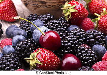 tasty summer fruits on a wooden table. Cherry, Blue berries,...