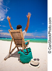 Young man relaxing in the wooden chair on white sand beach