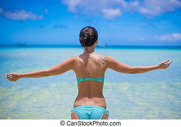 Back view of beautiful girl in swimsuit walking like a bird