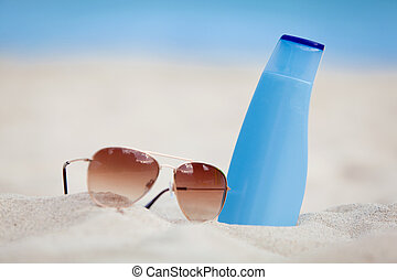 sunprotection summer holiday sunglasses and cream in sand...