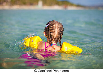 Adorable little girl swimming in the sea on tropical beach...