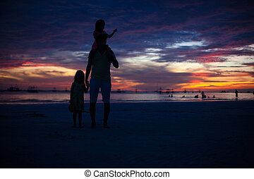 Dad and daughters silhouette in the sunset on the beach on Boracay