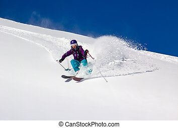 Woman Skier turns on a steep slope