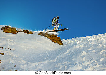 Skier jumps from a cliff during fast motion. Backlight of...