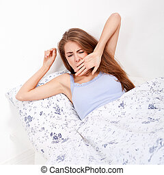 young attractive woman lying in bed yawing portrait tired