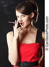 Woman and smoke - Stylish woman in red dress smoking...