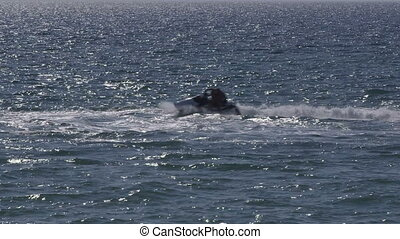 Riding on personal water craft - Man with child riding on...