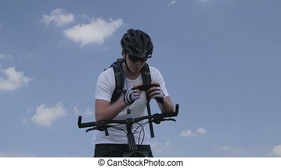 Mountain biker using smartphone - Mountain biker looking for...
