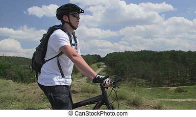 Mountain biker drinking water - Teen boy on bike drinking...