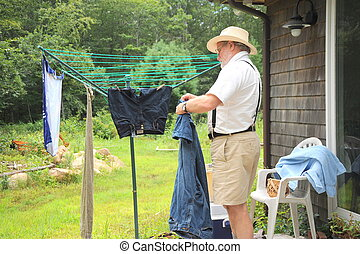Wash day. - Country gentleman hanging clothes on line to dry...
