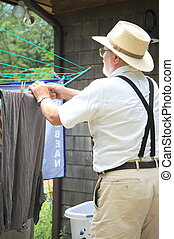 Wash day. - Country gentleman hanging clothes on line...