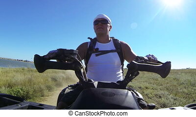 Tourist riding quad bike along the coast