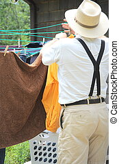 Wash day. - Country gentleman hanging clothes to line dry...