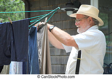 Wash day. - Country gentleman hanging clothes to line dry.
