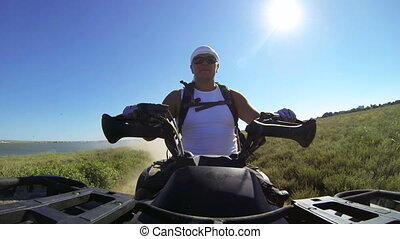Recreational trip on ATV - Man riding quad bike on a dusty...