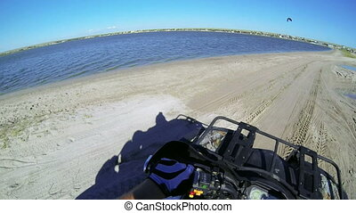 Riding quad bike through camping site on the beach POV