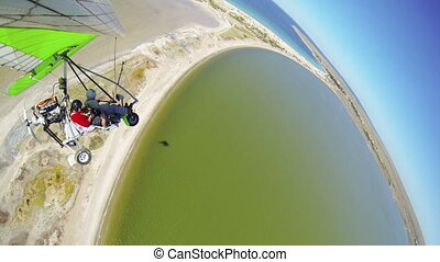 Flying on motorized hang glider over sea coast GoPro Hero3...