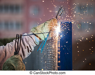 Arc welder worker in protective mask welding metal construction