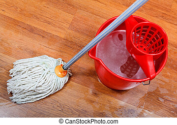 cleaning of wet floors by mop and red bucket with washing...