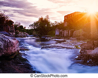 Summer evening on the mountain river with old palace ruines on background