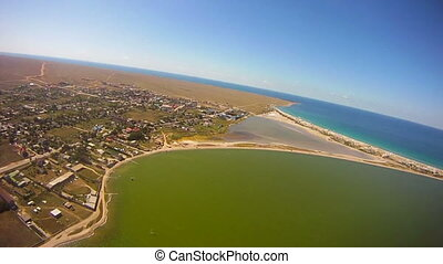 Aerial: Flying - Motorized hang glider flying over sea coast...