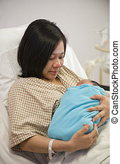 Asian mother and newborn baby girl in hospital