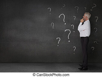 Thoughtful businessman standing in a dark room with question...