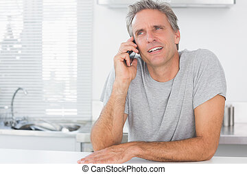 Happy man making phone call in kitchen