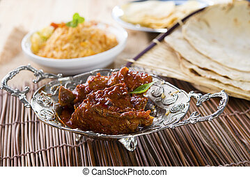 Butter chicken curry with basmati rice and various indian foods at background