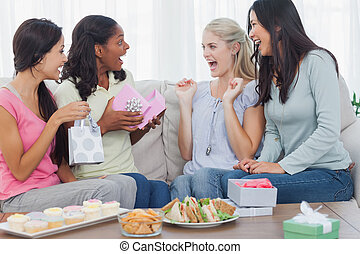 Friends offering gifts to woman during party at home on...