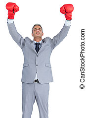 Cocky businessman posing with red boxing gloves on white...