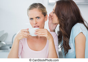 Brunette telling secret to her friend while drinking coffee...