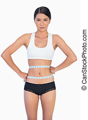 Slim woman measuring her waist