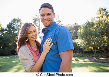 Smiling couple standing in a park