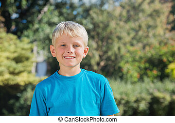 Blonde boy smiling at camera in the park on a sunny day