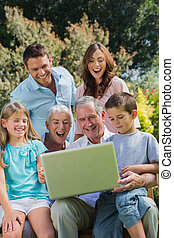Happy multi generation family with a laptop sitting in park...