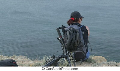 Woman traveler resting after bike trip on cliff by sea