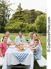 Multi generation family at picnic table having dinner...