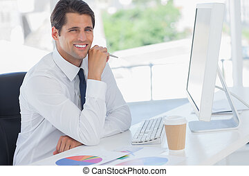 Cheerful businessman working on his computer