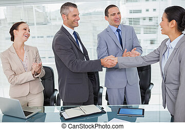 Smiling future workmates shaking hands in bright office
