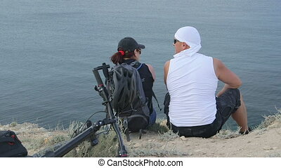 Couple of mountain bikers take a break on cliff by sea