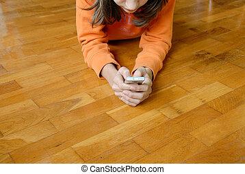 Teen girl with mobile phone - Teen girl lying on wooden...