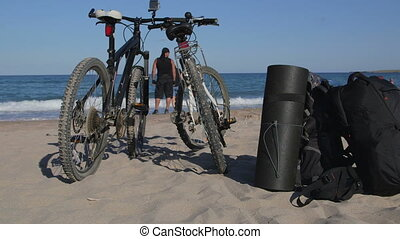 Couple of mountain bikers on the summer beach